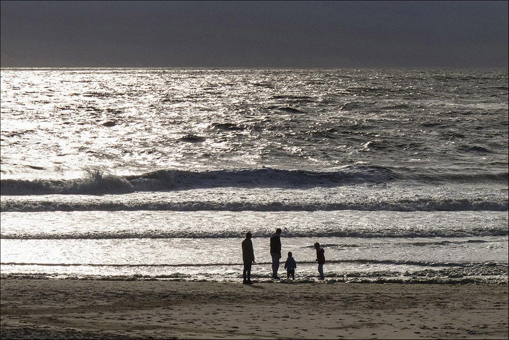 Spaziergänger bei untergehender Sonne am Strand von Westerland auf der Nordseeinsel Sylt (Landkreis Nordfriesland)).