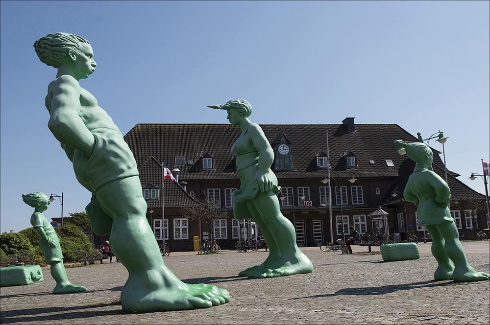 Reisende Riesen im Wind des Bildhauers Martin Wolke stehen seit 2001 auf dem Bahnhofsvorplatz in Westerland auf der Nordseeinsel Sylt (Landkreis Nordfriesland). Sie sind leuchtend grün und bestehen aus Fieberglas. Der Mann und die Frau sind vier, die Kinder zwei Meter hoch.