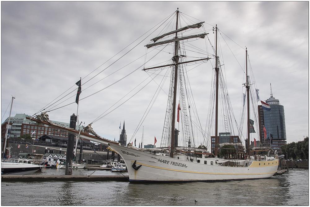 """Die """"Mare Frisium"""" (""""Friesisches Meer""""), ein historischer Dreimastmarstoppsegelschoner auf seinem Liegeplatz im Hamburger Hafen in St. Pauli. Es ist ein Schiff mit bewegter Geschichte. Ursprünglich wurde es 1916 als Segelschiff gebaut, als Zweimeister mit dem Namen """"Petronella"""" fuhr es auf die Nordsee zum Fischen. In den Fünfzigerjahren wurde es dann zum ersten Mal zum Frachtschiff umgebaut, die Masten wurden abgenommen und es hieß """"Helmut"""". Mitte der Neunzigerjahre wurde das Schiff wiederentdeckt, auf den ursprünglichen Segelrumpf wurde wieder eine traditionelle Takelage draufgesetzt und von da an trug es den Namen """"Mare Frisium"""". Das Schiff ist 50 Meter lang und 6,70 Meter breit. Es hat eine Segelfläche von 634 Quadratmeter. Der Hauptmast hat eine Gesamtlänge von 31 Meter. Touristen können heute mit dem Segler Ein- oder Mehrtagssegeltörns unternehmen."""