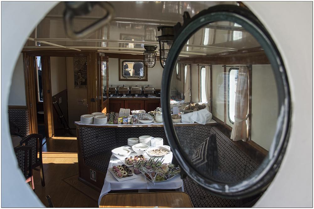 """Die """"Mare Frisium"""" (""""Friesisches Meer""""), ein historischer Dreimastmarstoppsegelschoner, ist ein Schiff mit bewegter Geschichte, auf dem Foto ein Blick durch ein Bullauge in einen Salon mit dedeckten Tischen. . Ursprünglich wurde es 1916 als Segelschiff gebaut, als Zweimeister mit dem Namen """"Petronella"""" fuhr es auf die Nordsee zum Fischen. In den Fünfzigerjahren wurde es dann zum ersten Mal zum Frachtschiff umgebaut, die Masten wurden abgenommen und es hieß """"Helmut"""". Mitte der Neunzigerjahre wurde das Schiff wiederentdeckt, auf den ursprünglichen Segelrumpf wurde wieder eine traditionelle Takelage draufgesetzt und von da an trug es den Namen """"Mare Frisium"""". Das Schiff ist 50 Meter lang und 6,70 Meter breit. Es hat eine Segelfläche von 634 Quadratmeter. Der Hauptmast hat eine Gesamtlänge von 31 Meter. Touristen können heute mit dem Segler Ein- oder Mehrtagssegeltörns unternehmen."""