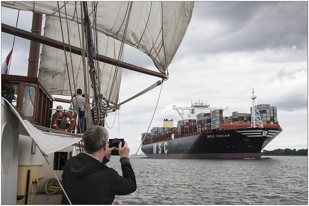 """Die """"Mare Frisium"""" (""""Friesisches Meer""""), ein historischer Dreimastmarstoppsegelschoner, bei einem Segeltörn auf der Elbe in Hamburg. Auf dem Foto das 2015 gebaute Containerschiff """"MSC Oscar"""", eines der größten Containerschiffe der Welt. Das 395 Meter lange Schiff kann 19200 Container befördern. Die """"Mare Frisium"""" ist ein Schiff mit bewegter Geschichte. Ursprünglich wurde es 1916 als Segelschiff gebaut, als Zweimeister mit dem Namen """"Petronella"""" fuhr es auf die Nordsee zum Fischen. In den Fünfzigerjahren wurde es dann zum ersten Mal zum Frachtschiff umgebaut, die Masten wurden abgenommen und es hieß """"Helmut"""". Mitte der Neunzigerjahre wurde das Schiff wiederentdeckt, auf den ursprünglichen Segelrumpf wurde wieder eine traditionelle Takelage draufgesetzt und von da an trug es den Namen """"Mare Frisium"""". Das Schiff ist 50 Meter lang und 6,70 Meter breit. Es hat eine Segelfläche von 634 Quadratmeter. Der Hauptmast hat eine Gesamtlänge von 31 Meter. Touristen können heute mit dem Segler Ein- oder Mehrtagssegeltörns unternehmen."""