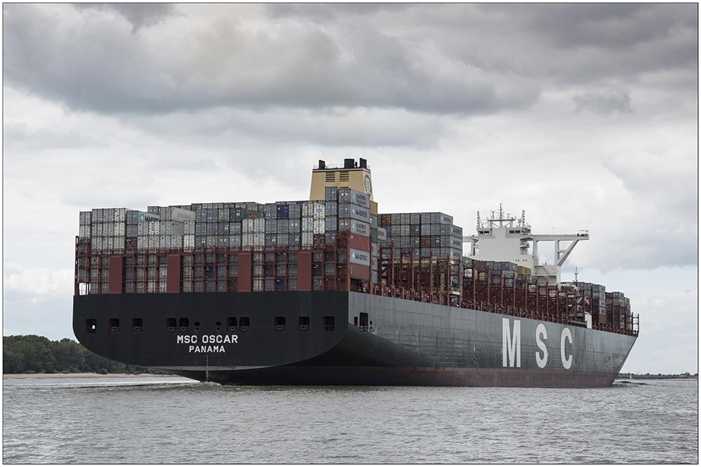 """Das 2015 gebaute Containerschiff """"MSC Oscar"""", eines der größten Containerschiffe der Welt, auf der Elbe vom Hamburger Hafen Richtung Nordsee unterwegs. Das 395 Meter lange Schiff kann 19200 Container befördern. Der Tiefgang beträgt bei voller Ladung 16 Meter. Gebaut wurde das Schiff in Südkorea."""