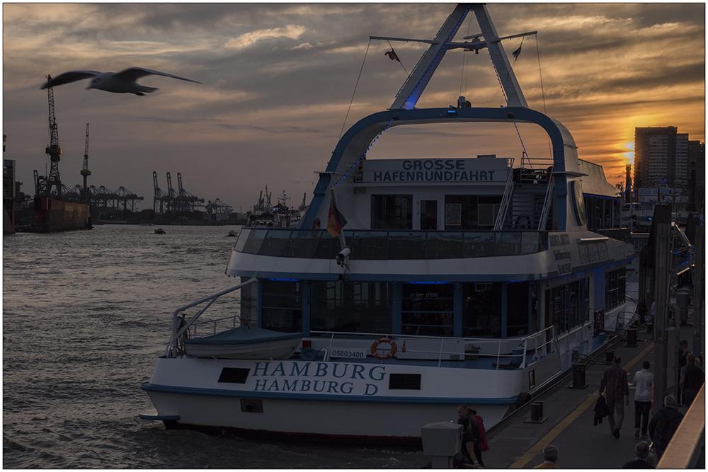 Sonnenuntergang an der Elbe im Hamburger Hafen. Im Vordergrund ein Fahrgastschiff für Hafenrundfahrten, im Hintergrund Kräne des Containerhafens.