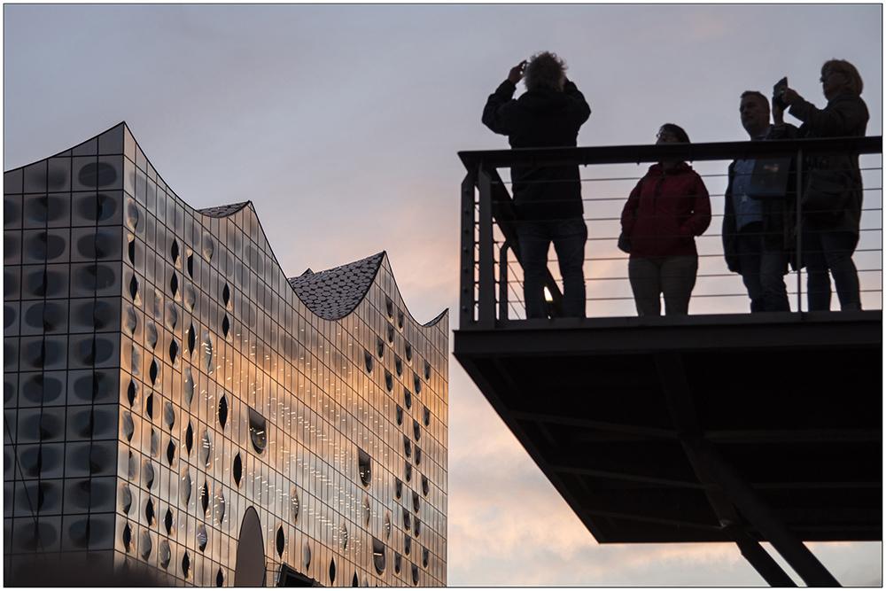 Touristen fotografieren während des Sonnenuntergangs die Elbphilharmonie. Die Elbphilharmonie ist ein seit April 2007 in Bau befindliches Konzerthaus in der HafenCity in Hamburg. Das 110 Meter hohe Gebäude wird vom Baudienstleister Hochtief errichtet. Der Entwurf und die weitere Hochbauplanung des Gebäudes stammt vom Basler Architekturbüro Herzog & de Meuron. Bauherr ist formell die Elbphilharmonie Hamburg Bau GmbH & Co. KG, deren Kommanditist und Hauptgeldgeber das Land Hamburg ist. Die Fertigstellung des Gebäudes war für 2010 geplant. Die Eröffnung soll nun im Januar 2017 erfolgen. Die Baukosten stiegen von 77 Millionen Euro auf jetzt 575 Millionen Euro.