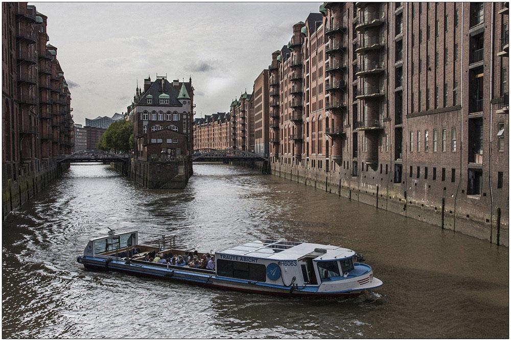 Das Wasserschloss in der Speicherstadt in Hamburg. Das Gebäude liegt zwischen dem Wandrahmsfleet (rechts) und dem Holländischbrookfleet (links). Es wurde 1905 erbaut und diente als Unterkunft und Werkstatt für Hafenarbeiter. Heute beherbergt es u.a. ein Restaurant. Sie ist ein historischer Lagerhauskomplex im Hamburger Hafen. Seit 1991 steht sie unter Denkmalschutz und sie gehört UNESCO-Weltkulturerbe. Die Speicherstadt wurde ab 1883 auf den ehemaligen Elbinseln und Wohnquartieren Kehrwieder und Wandrahm als Teilstück des Hamburger Freihafens erbaut, der erste Abschnitt war 1888 fertiggestellt. Die Speicherstadt steht auf der rund 26 Hektar großen Fläche (einschließlich der Fleete) der ehemaligen Elbinseln Kehrwieder und Wandrahm, auf einer Länge von etwa 1,5 Kilometer und 150 bis 250 Metern Breite im nordöstlichen Hamburger Hafen. Sie zieht sich von der Kehrwiederspitze und dem Sandtorhöft im Westen bis zum ehemaligen Teerhof bei der Oberbaumbrücke im Osten. Dabei wird sie von sechs Fleeten durchzogen.