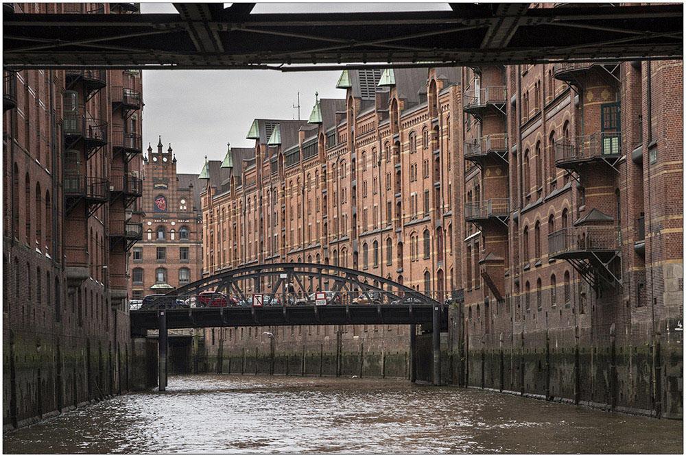 Die Speicherstadt in Hamburg. Sie ist ein historischer Lagerhauskomplex im Hamburger Hafen. Seit 1991 steht sie unter Denkmalschutz und sie gehört UNESCO-Weltkulturerbe. Die Speicherstadt wurde ab 1883 auf den ehemaligen Elbinseln und Wohnquartieren Kehrwieder und Wandrahm als Teilstück des Hamburger Freihafens erbaut, der erste Abschnitt war 1888 fertiggestellt. Die Speicherstadt steht auf der rund 26 Hektar großen Fläche (einschließlich der Fleete) der ehemaligen Elbinseln Kehrwieder und Wandrahm, auf einer Länge von etwa 1,5 Kilometer und 150 bis 250 Metern Breite im nordöstlichen Hamburger Hafen. Sie zieht sich von der Kehrwiederspitze und dem Sandtorhöft im Westen bis zum ehemaligen Teerhof bei der Oberbaumbrücke im Osten. Dabei wird sie von sechs Fleeten durchzogen.