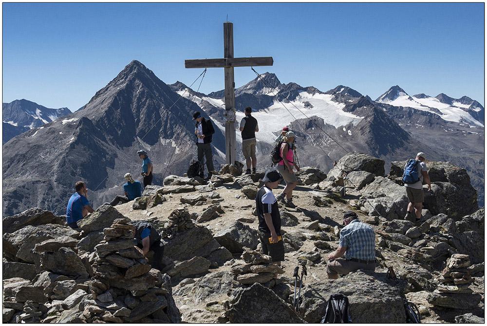 Auf dem Gipfel des Wilden Mannle (3019 Meter) oberhalb von Vent (1895 Meter) in den Ötztaler Alpen in Tirol, Österreich. Hinter dem Gipfelkreuz die 3457 Meter hohe Kreuzspitze.