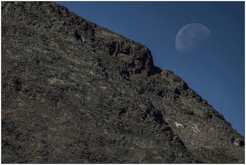 Der Mond über den Felsen der Berge an der Hohe-Mut-Alm über Obergurgl im UNESCO-Biosphärenpark Gurgler Kamm in den Ötztaler Alpen in Tirol, Österreich.