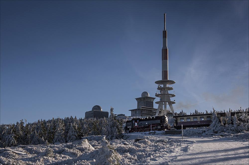 Mit 1141 Meter Höhe ist der Brocken der höchste Berg Norddeutschlands und des Mittelgebirges Harz. Der Berg liegt im Hochharz im Nationalpark Harz und im Naturpark Harz/Sachsen-Anhalt. Der Brocken wurde umfangreich für Überwachungs- und Spionagezwecke genutzt. Auf dem Gipfel befanden sich zwei große und leistungsfähige Abhöranlagen (Foto). Eine gehörte dem sowjetischen Militärgeheimdienst GRU und war damit zugleich der westlichste Vorposten Moskaus, die andere war der Hauptabteilung III des Ministerium für Staatssicherheit der DDR unterstellt. Ab August 1961 wurde der Brocken, der im unmittelbaren Grenzgebiet der DDR zur Bundesrepublik Deutschland lag, zum militärischen Sperrgebiet erklärt und war somit für die Bevölkerung nicht mehr zugänglich. Auf dem Foto auch ein Zug der Brockenbahn, die den Gipfel umrundet. Der Bahnhof liegt auf einer Höhe von 1125 Meter.