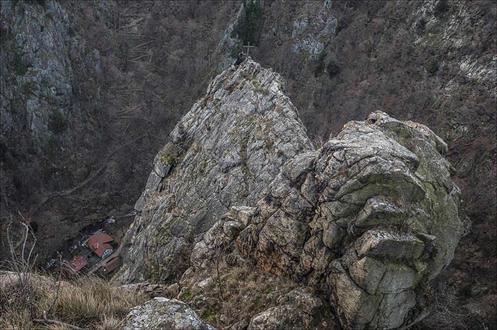 Der Rosstrappenfelsen mit Gipfelkreuz im Naturschutzgebiet im Bodetal bei Thale (Landkreis Harz). Im Talgrund einige Häuser an der Bode, die auf dem Brocken entspringt.