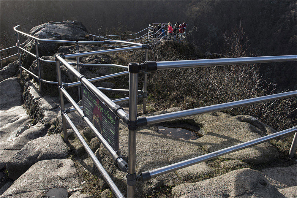 Geländer auf dem Rosstrappenfelsen sorgen dafür, dass Besucher ohne Gefahr in das Bodetal bei Thale im Naturschutzgebiet Bodetal schauen können. Im Vordergrund befindet sich der Hufabdruck, die das Pferd von Brunhilde hinterlassen hat, als sie auf der Flucht das Bodetal übersprang (Rosstrappen-Sage).